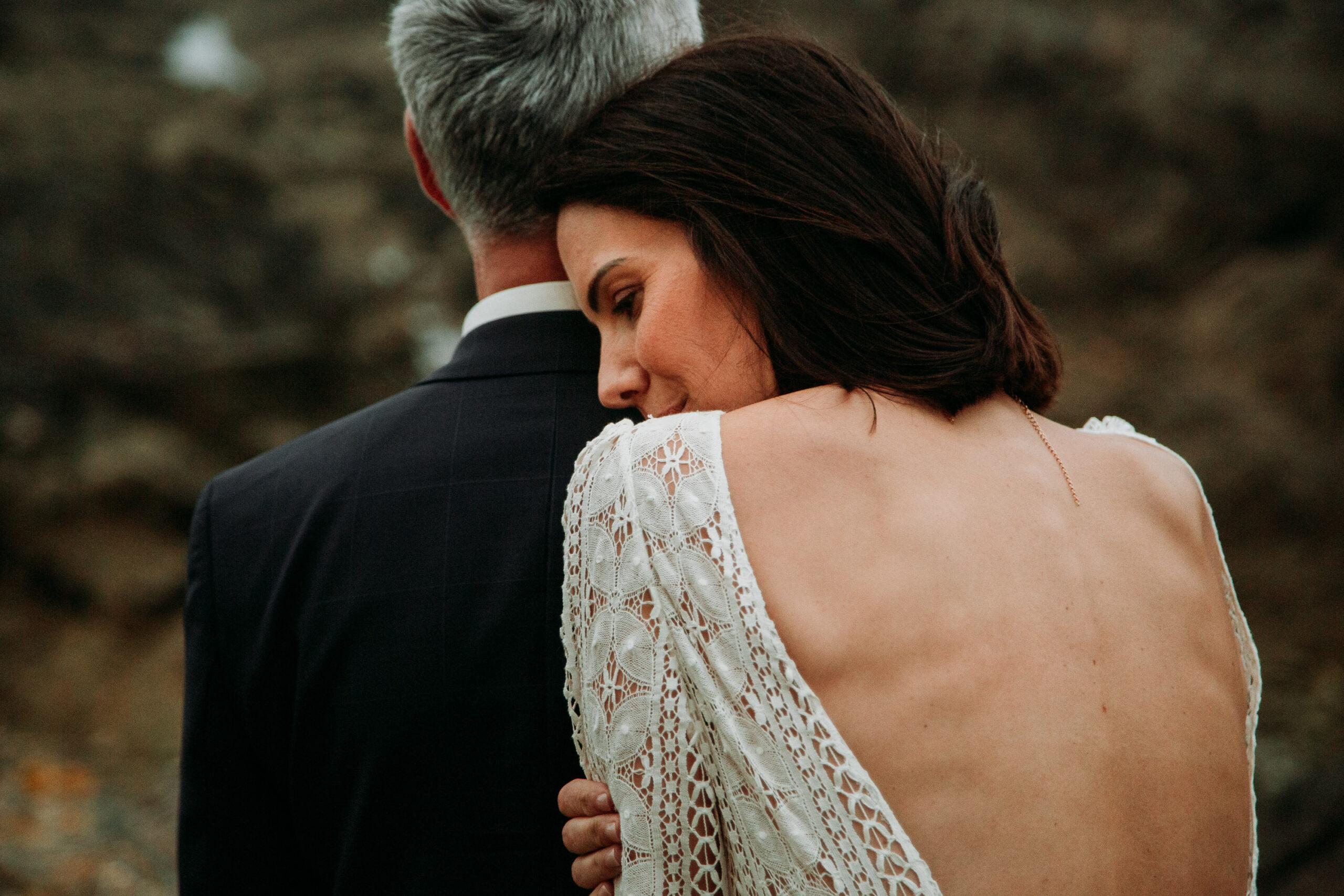 photo de mariage d'un couple, la mariée a la tête posée sur son époux. prise en bord de mer sur la cote atlantique vers pornic.