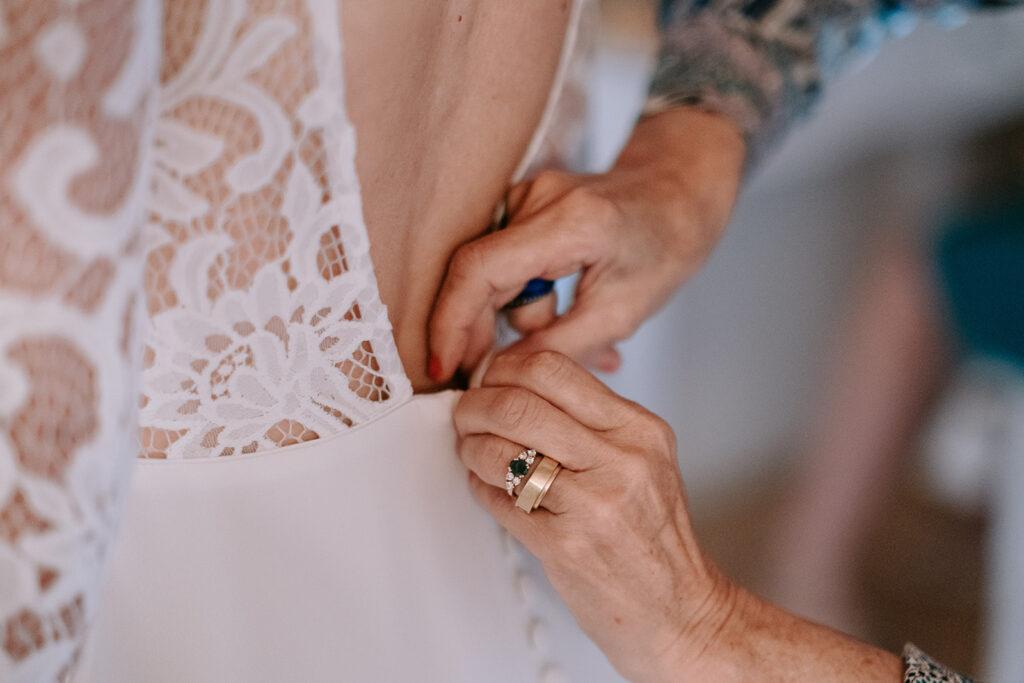 préparatifs de la mariée avec la mère de la mariée - le boutonnage de la robe